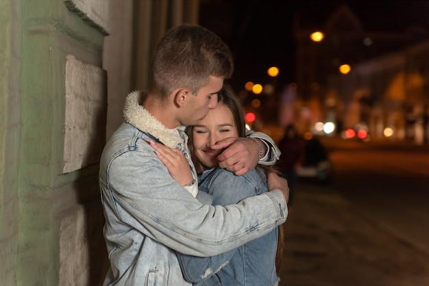 幸せな若いカップルは、夜の街の背景を抱いています。男は抱擁し、彼のガールフレンドにキスします。通りのロマンチックなデート。