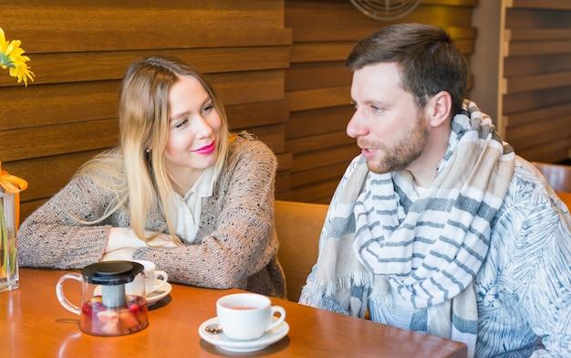 행복 한 젊은 커플 이야기와 커피를 마시고 카페에 앉아있는 동안 웃 고.