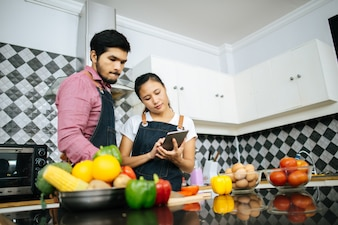 Happy young couple is using digital tablet for looking method of cooking