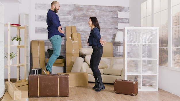 Happy young couple jumping in their new apartment. excited about their new apartment. suitcases in apartment.