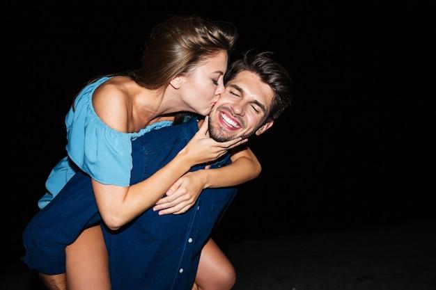 Счастливая молодая пара целоваться и веселиться на пляже ночью
