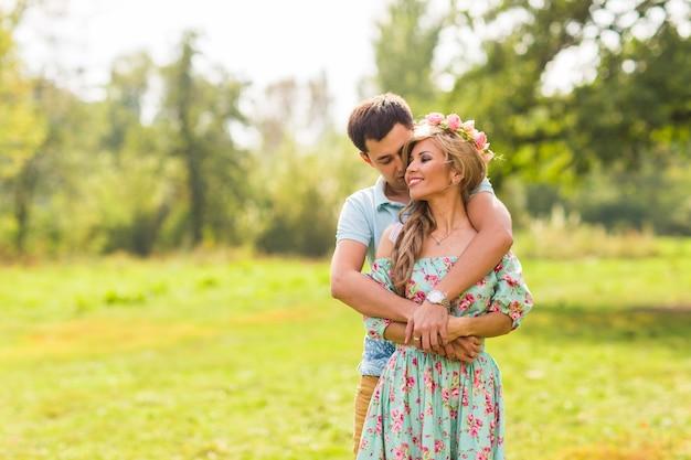 幸せな若いカップルがキスをし、自然を抱き締めます。