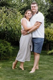 幸せな若いカップルが夏の日に屋外でキスとハグ