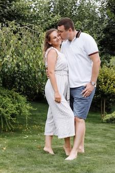 夏の日に屋外でキスとハグ幸せな若いカップル。