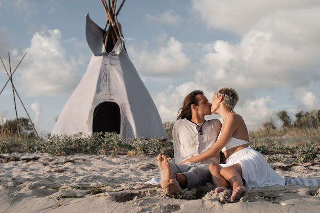 Happy young couple kissing on the beach at wigwam
