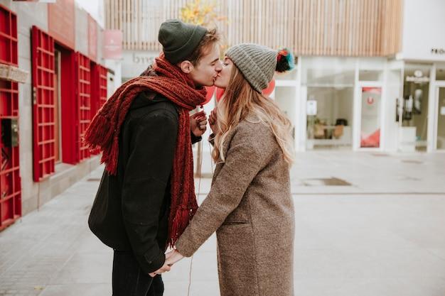 幸せな若いカップルは、通りにキス