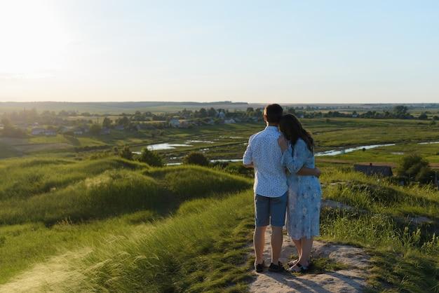 맑은 하늘과 산 꼭대기에 키스 행복 젊은 부부. 행복한 가족