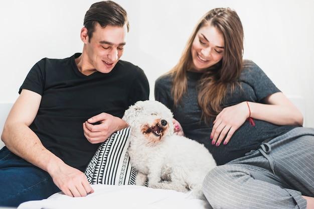 Счастливый молодая пара, глядя на дружественных пудель игрушка, сидя на кровати