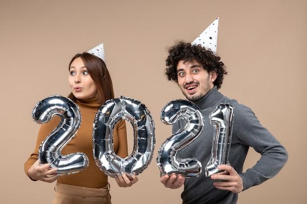 さまざまな方向を見ている幸せな若いカップルは、カメラの女の子のショーと灰色の男と新年の帽子のポーズを着ています