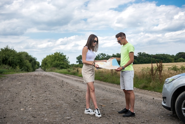 Happy young couple looking at road map near car. summer time