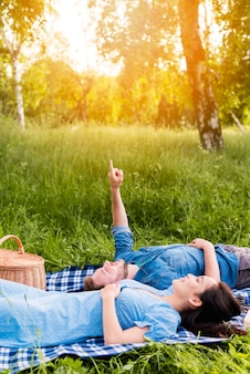 Happy young couple looking at sky while lying on blanket in nature
