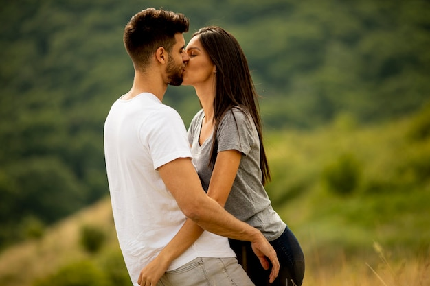 Happy young couple in love at the grass field on a summer day