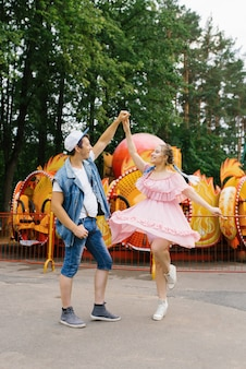 Happy young couple in love having fun in an amusement park and dancing