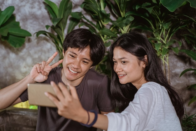 Happy young couple in love having fun and taking selfie portrait on outdoor cafe at night