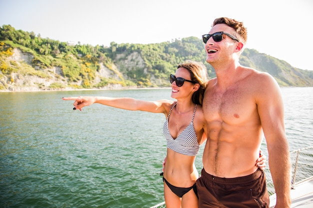 Happy young couple in love hugging on sail boat floating on the sea. young people having fun at holiday, exclusive vacation