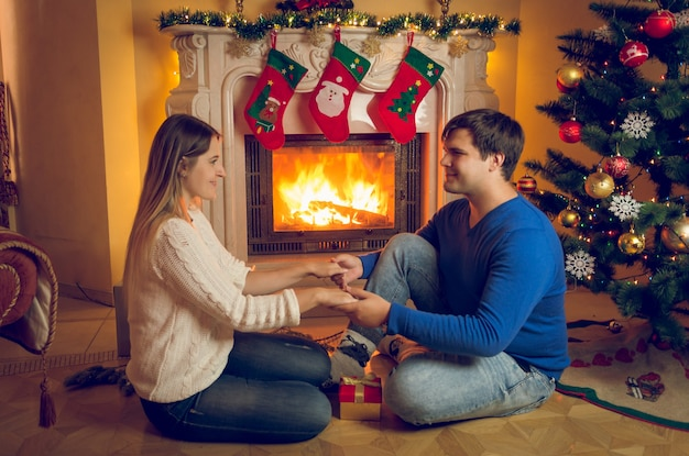 Happy young couple in love sitting at fireplace and holding hands