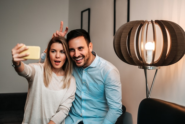 Happy young couple in love takes funny selfie portrait.