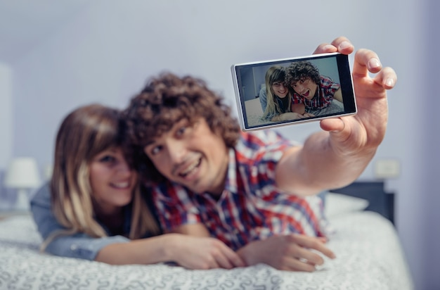 Happy young couple in love taking a selfie with smartphone lying over a bed. selective focus on the phone.