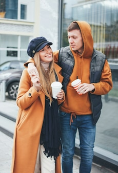 Happy young couple in love teenagers friends dressed in casual style walking together on city street in cold season