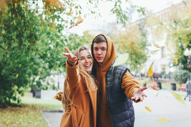 Happy young couple in love teenagers friends dressed in casual style walking together and throws leaves at camera, autumn city street