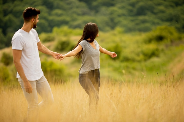 Happy young couple in love walking through grass field on a summer day