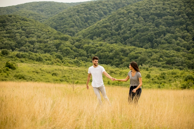 Happy young couple in love walking through grass field