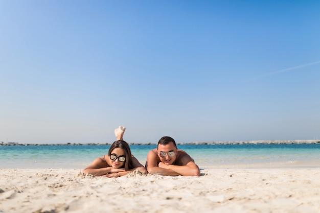 熱帯のビーチで横になっている幸せな若いカップル