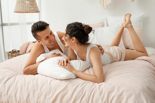 Счастливая молодая пара, лежа на кровати у себя дома