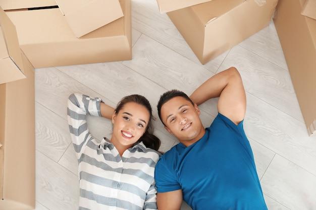 Счастливая молодая пара, лежа на полу в своей новой квартире возле движущихся ящиков