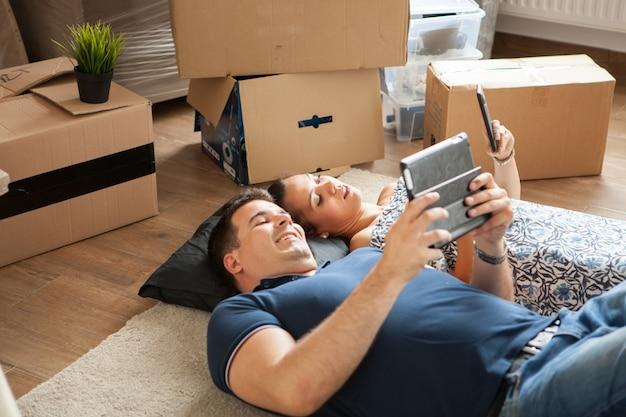 이동 상자 근처 바닥에 누워 행복 한 젊은 커플. 새 집으로 이사하는 젊은 가족.