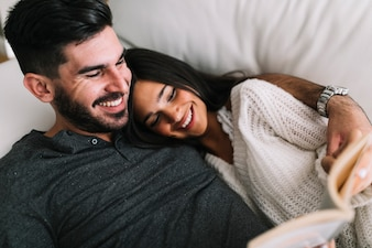 Happy young couple lying on sofa reading book