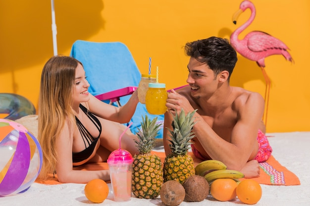 Happy young couple lying with cocktails on beach in studio