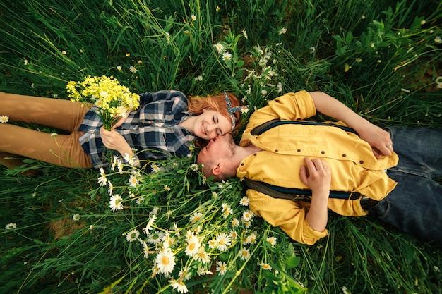 Счастливая молодая пара мужчина и женщина рыжий, лежа на ярко-зеленой траве в летний день, вид сверху. любовная история.