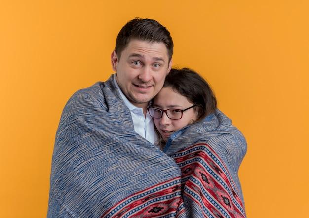 오렌지 벽 위에 서있는 그의 얼어 붙은 여자 친구가 따뜻한 담요로 덮고있는 행복 한 젊은 커플 남자