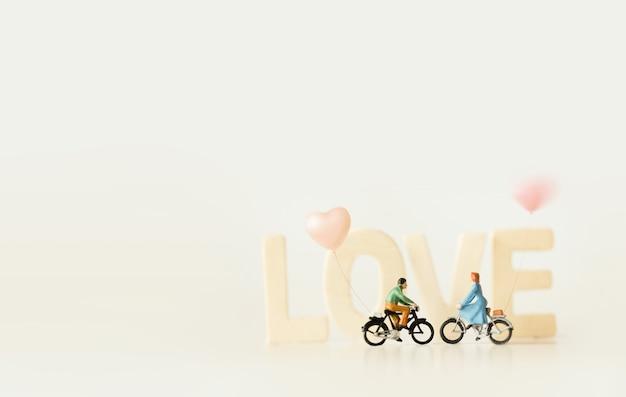 Счастливая молодая пара (миниатюра) на велосипедной прогулке с текстом «любовь». день святого валентина фон с винтажной цветовой темой.