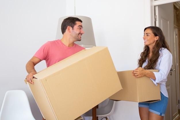 Счастливая молодая пара переезжает в новую квартиру, несет картонные коробки, смотрит вокруг и улыбается