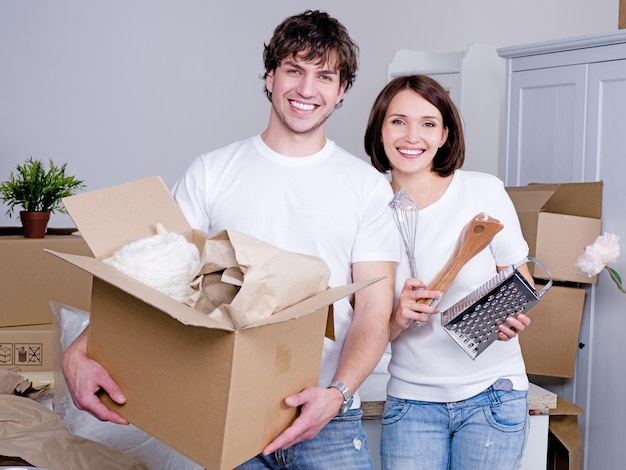 Happy young couple moving to a new flat