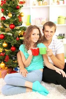 Счастливая молодая пара возле елки дома
