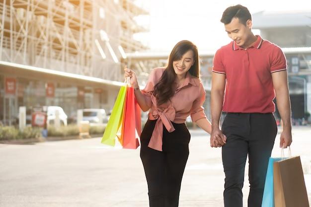 Счастливая молодая пара покупателей, идущих по торговой улице и держа в руке красочные хозяйственные сумки.