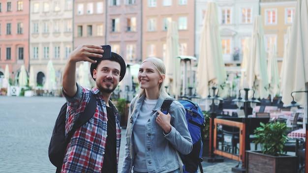Счастливая молодая пара туристов, делающих селфи на смартфоне в центре города. у них есть туристические сумки.
