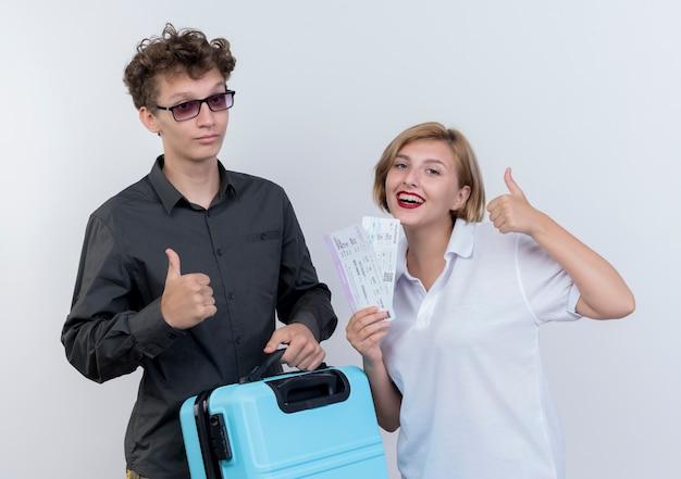 Счастливая молодая пара туристов мужчина и женщина, держащая чемодан и авиабилеты, улыбаясь, показывает палец вверх над белой