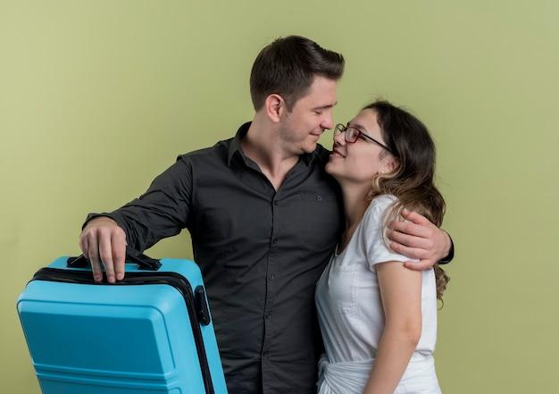 Счастливая молодая пара туристов мужчина и женщина, держащая чемодан, глядя друг на друга, обниматься за свет