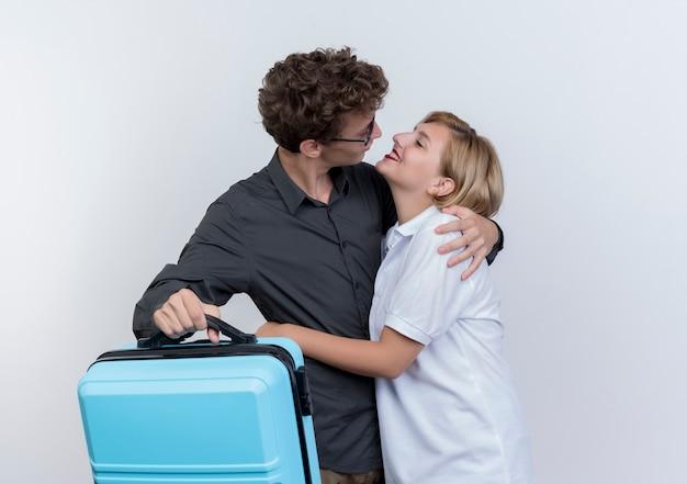 Счастливая молодая пара туристов мужчина и женщина, держащая чемодан, глядя друг на друга, обниматься над белой стеной