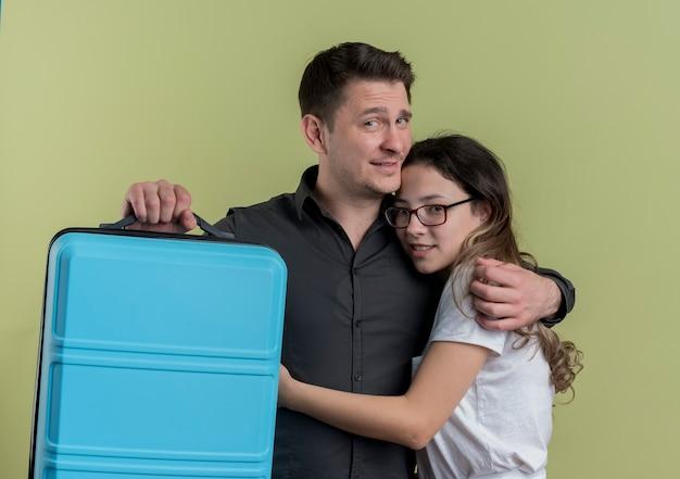 Счастливая молодая пара туристов мужчина и женщина, держащая чемодан, улыбаясь и обнимаясь над светлой стеной