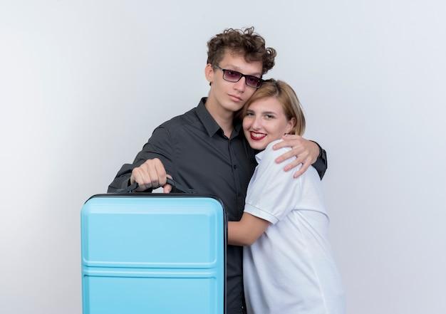 Счастливая молодая пара туристов мужчина и женщина, держащая чемодан, улыбаясь и обнимая над белой стеной