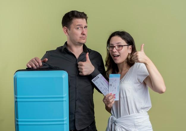 Счастливая молодая пара туристов мужчина и женщина, держащая чемодан, улыбаясь, показывает палец вверх, стоя над светлой стеной