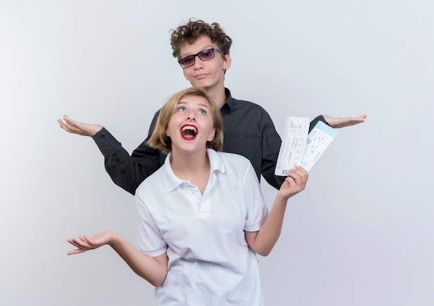 관광객 남자와 여자의 행복 한 젊은 커플 항공 티켓이 함께 흰 벽 위에 서있는 재미