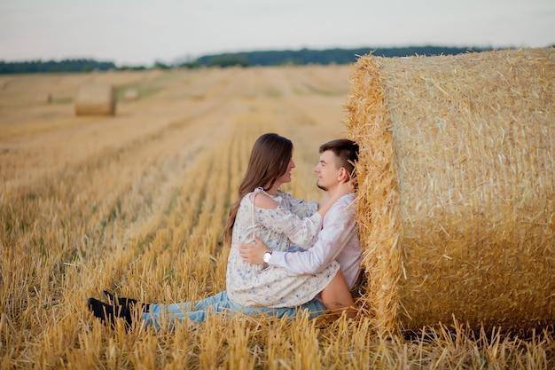 Счастливая молодая пара на соломе, концепция романтических людей, красивый пейзаж, летний сезон.