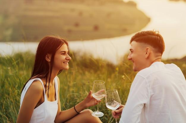 ピクニックでリラックスした丘の上の幸せな若いカップル。