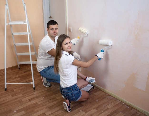 Счастливая молодая пара рисует интерьерную стену нового дома или квартиры они держат валики с краской